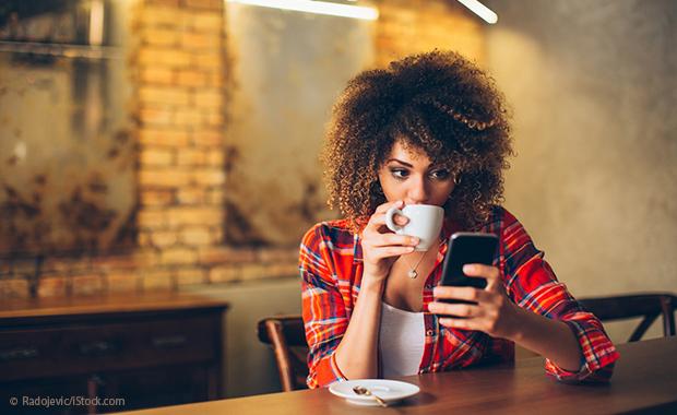 Junge Frau trinkt Kaffee und schaut auf ihr Smartphone